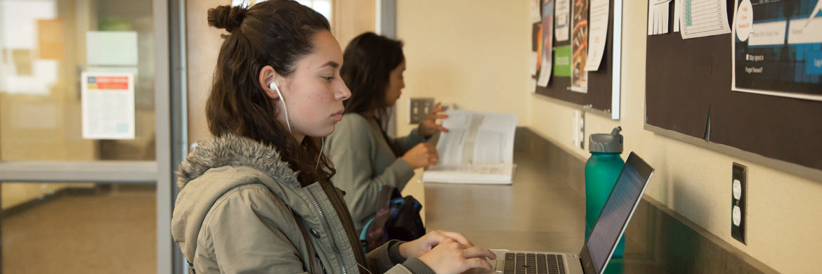 woman with headphones stands at counter in iCommons typing on laptop